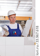 Contractor installing ceramic tile. Стоковое фото, фотограф Яков Филимонов / Фотобанк Лори