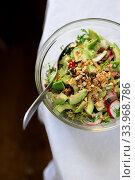 Купить «salad in a transparent bowl of avocado, walnuts, green salad, radish French mustard on a table with a white tablecloth. View from above», фото № 33968786, снято 29 апреля 2020 г. (c) Tetiana Chugunova / Фотобанк Лори