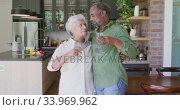 Купить «Senior African American husband and mixed race wife drinking a beverage together at home», видеоролик № 33969962, снято 19 февраля 2020 г. (c) Wavebreak Media / Фотобанк Лори