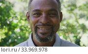 Купить «Senior African American man smiling and looking at the camera», видеоролик № 33969978, снято 19 февраля 2020 г. (c) Wavebreak Media / Фотобанк Лори