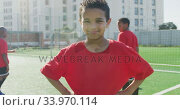 Купить «Mixed race soccer kid in red smiling and looking at camera», видеоролик № 33970114, снято 18 октября 2019 г. (c) Wavebreak Media / Фотобанк Лори