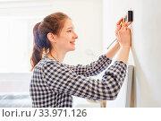 Junge Frau mit Bleistift und Wasserwaage an der Wand beim DIY Renovieren ihrer Wohnung. Стоковое фото, фотограф Zoonar.com/Robert Kneschke / age Fotostock / Фотобанк Лори