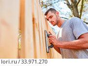 Junger Mann als Handwerker Azubi oder als Heimwerker beim Zaun abschleifen im Garten. Стоковое фото, фотограф Zoonar.com/Robert Kneschke / age Fotostock / Фотобанк Лори