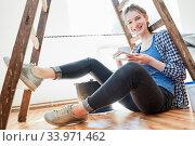Junge Frau bei der Renovierung macht Pause und trinkt eine Tasse Kaffee auf dem Parkett. Стоковое фото, фотограф Zoonar.com/Robert Kneschke / age Fotostock / Фотобанк Лори