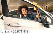 Afrikanische Frau poliert Tür vom Auto mit Tuch im Autohaus. Стоковое фото, фотограф Zoonar.com/Robert Kneschke / age Fotostock / Фотобанк Лори