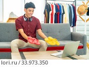 Купить «Young asian male online merchant fashion blogger using laptop computer to recording live vlog video for review casual wear clothes. Online Influencer on social media concept.», фото № 33973350, снято 3 июля 2020 г. (c) easy Fotostock / Фотобанк Лори