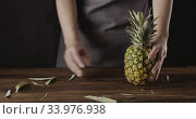 Купить «Woman in a kitchen apron put fresh juicy natural pineapple on a wooden board with one cutting quarter. Motion, 4K UHD video, 3840, 2160p.», видеоролик № 33976938, снято 3 августа 2020 г. (c) Ярослав Данильченко / Фотобанк Лори