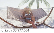 Купить «Caucasian woman lying on a hammock on the beach», видеоролик № 33977054, снято 25 февраля 2020 г. (c) Wavebreak Media / Фотобанк Лори