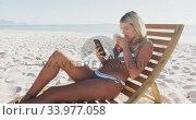 Caucasian woman sitting on a sunbed and using her smartphone on the beach. Стоковое видео, агентство Wavebreak Media / Фотобанк Лори