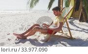 Caucasian man sitting on a sunbed and using his laptop on the beach. Стоковое видео, агентство Wavebreak Media / Фотобанк Лори