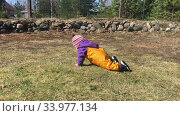 Купить «Caucasian little baby boy crawling on ground in backyard, wearing trousers from waterproof material», видеоролик № 33977134, снято 18 мая 2020 г. (c) Кекяляйнен Андрей / Фотобанк Лори