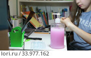 School age girl disinfecting her hands with liquid antiseptic while doing home exercises at the desk. Стоковое видео, видеограф Кекяляйнен Андрей / Фотобанк Лори