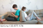 Pre-teen sister and brother gaming online with cellphones while sitting at home, children wearing safety masks, sitting back to back on sofa. Стоковое видео, видеограф Кекяляйнен Андрей / Фотобанк Лори