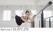 Купить «Caucasian female ballet dancer stretching up by the mirror in a bright studio», видеоролик № 33977270, снято 24 октября 2019 г. (c) Wavebreak Media / Фотобанк Лори