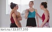 Купить «Caucasian ballet female dancers standing together, chatting and laughing during a ballet class», видеоролик № 33977310, снято 24 октября 2019 г. (c) Wavebreak Media / Фотобанк Лори