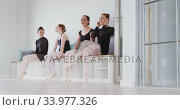 Купить «Caucasian ballet female dancers sitting on a bench and laughing, during a ballet class», видеоролик № 33977326, снято 24 октября 2019 г. (c) Wavebreak Media / Фотобанк Лори