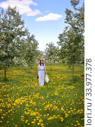 Купить «A young girl walks with a bag in the garden on green grass and blooming dandelions», фото № 33977378, снято 29 мая 2020 г. (c) Максим Мицун / Фотобанк Лори
