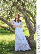 Купить «A beautiful girl in a blue dress and a straw hat stands under a white Apple tree in full bloom», фото № 33977386, снято 29 мая 2020 г. (c) Максим Мицун / Фотобанк Лори