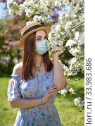 Купить «A beautiful girl in a medical mask, blue dress and straw hat stands by a blooming white Apple tree in the garden», фото № 33983686, снято 29 мая 2020 г. (c) Максим Мицун / Фотобанк Лори