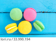 Купить «Colorful macaroni or macaroons cookies on blue wooden vintage background. top view», фото № 33990194, снято 14 июля 2020 г. (c) easy Fotostock / Фотобанк Лори