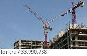 Купить «Quick motion footage of a large construction site with several busy cranes on the background of clear blue sky», видеоролик № 33990738, снято 13 июня 2020 г. (c) Алексей Кузнецов / Фотобанк Лори