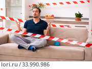 Купить «Young man feeling bored at home in self-isolation concept», фото № 33990986, снято 1 апреля 2020 г. (c) Elnur / Фотобанк Лори