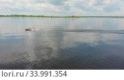 Two men riding motor boat on river - green islands on the water. Стоковое видео, видеограф Константин Шишкин / Фотобанк Лори