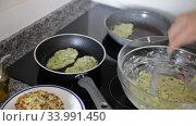 Купить «Image of process frying zucchini pancakes in frying pan in kitchen», видеоролик № 33991450, снято 29 февраля 2020 г. (c) Яков Филимонов / Фотобанк Лори