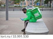 Курьер сервиса доставки еды Delivery Club на улице в Москве. Редакционное фото, фотограф Victoria Demidova / Фотобанк Лори