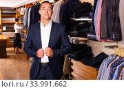 Купить «Portrait of male client choosing classic jacket in the mall», фото № 33991662, снято 7 июля 2020 г. (c) Яков Филимонов / Фотобанк Лори