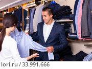 Seller helps buyer to choose a shirt in the store. Стоковое фото, фотограф Яков Филимонов / Фотобанк Лори