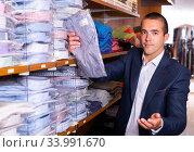 Купить «Male seller lays out shirts on shelves in clothing store», фото № 33991670, снято 7 июля 2020 г. (c) Яков Филимонов / Фотобанк Лори