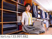 Friendly chinese woman tailor at work desk in clothing store. Стоковое фото, фотограф Яков Филимонов / Фотобанк Лори