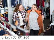 Women trying coat in clothing boutique. Стоковое фото, фотограф Яков Филимонов / Фотобанк Лори