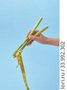 Купить «Female's hand with asparagus sticks is taking measure tape.», фото № 33992302, снято 14 мая 2020 г. (c) Ярослав Данильченко / Фотобанк Лори