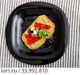 Top view of sandwich with guacamole, canned fish, pepper on black plate. Стоковое фото, фотограф Яков Филимонов / Фотобанк Лори