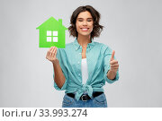 smiling woman with green house showing thumbs up. Стоковое фото, фотограф Syda Productions / Фотобанк Лори