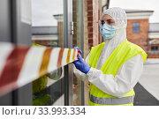 Купить «healthcare worker sealing door with caution tape», фото № 33993334, снято 24 апреля 2020 г. (c) Syda Productions / Фотобанк Лори