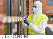 Купить «healthcare worker sealing door with caution tape», фото № 33993466, снято 24 апреля 2020 г. (c) Syda Productions / Фотобанк Лори