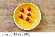 Five red radishes on a yellow plate on a wooden tabletop. Стоковое фото, фотограф Евгений Харитонов / Фотобанк Лори