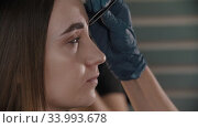 Master adding finishing touches to the tinted eyebrows - plucks hairs. Стоковое видео, видеограф Константин Шишкин / Фотобанк Лори