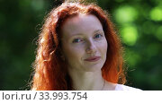 Portrait of a red-haired young adult woman with hair flowing in the light wind on the natural background of the park on a sunny summer day. Стоковое видео, видеограф Алексей Кузнецов / Фотобанк Лори
