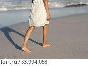 Купить «Mixed race woman bare feet touching the sand on beach on a sunny day», фото № 33994058, снято 25 февраля 2020 г. (c) Wavebreak Media / Фотобанк Лори