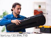 Купить «Young male repairman repairing violin», фото № 33994710, снято 25 октября 2019 г. (c) Elnur / Фотобанк Лори