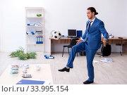 Купить «Young male employee playing football in the office», фото № 33995154, снято 13 сентября 2019 г. (c) Elnur / Фотобанк Лори