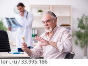 Купить «Young male doctor and old patient in antismoking concept», фото № 33995186, снято 9 сентября 2019 г. (c) Elnur / Фотобанк Лори
