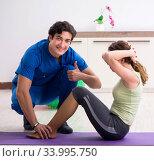 Купить «Fitness instructor helping sportsman during exercise», фото № 33995750, снято 10 июля 2018 г. (c) Elnur / Фотобанк Лори