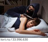 Купить «Burglar breaking into house at night to bedroom with sleeping wo», фото № 33996630, снято 9 августа 2017 г. (c) Elnur / Фотобанк Лори