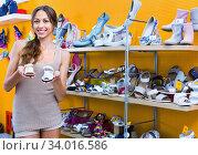 Portrait of woman looking after pair of shoes for kid. Стоковое фото, фотограф Яков Филимонов / Фотобанк Лори
