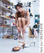 woman trying on sandals in shoe store. Стоковое фото, фотограф Яков Филимонов / Фотобанк Лори